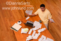 Photo of a man paying his bills at home. He is overwhelmed with the task. He is holding up bills in both hands and the camera is looking down from above.